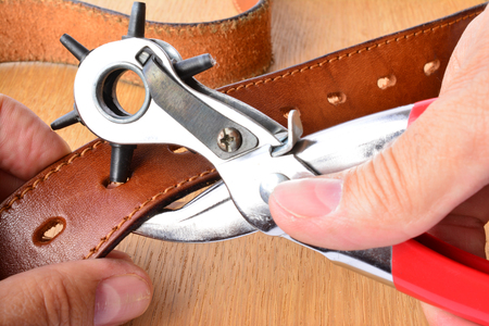 girdle: Leather girdle perforation, punch tool and new leather belt in craftmans hands over wooden background Stock Photo