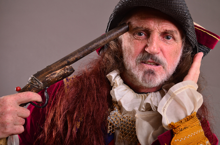 holding gun to head: Portrait of old captain pirate, holding his gun pointed to his head, ready to commit suicide Stock Photo
