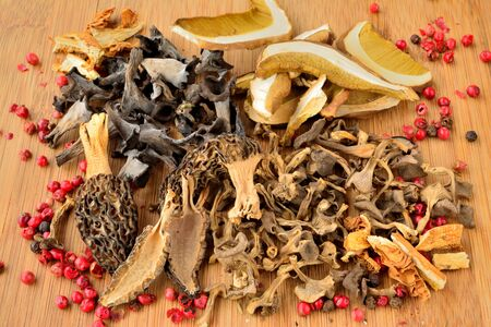 horn of plenty: Various dried mushrooms, Penny Bun or Cep, Morels, Horn of Plenty mushrooms, Golden Bootleg mushrooms and Trumpet Chanterelle mushrooms, left on wooden chopping board with some red pepper