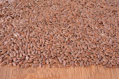 close uo: Pile of flax seed on wooden chopping board, close uo view, shallow depth of field