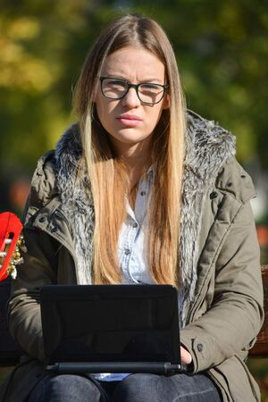 conceived: Young, beautiful, conceived blonde girl solving a problem during  work on her lap top outdoors in bright sunny autumn day