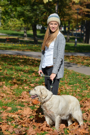 retreiver: Young, cute girl wearing cardigan and woolen cap, standing in autumn leaves in a park together with her pet, golden retreiver dog
