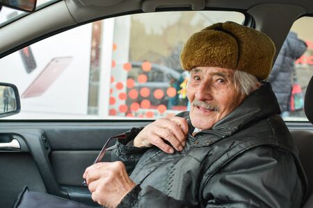 vital: Vital elderly man with fur hat  in a car, smiling and holding glasses during drive