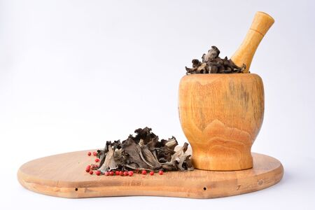 horn of plenty: Dried edible, aromatic  Horn on plenty mushrooms with red pepper in bamboo wooden mortar, on bamboo chopping board, over white background Stock Photo