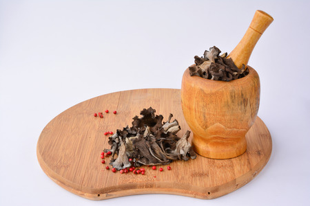 horn of plenty: Dried edible, aromatic  Horn on plenty mushrooms in bamboo wooden mortar, on bamboo chopping board, over white