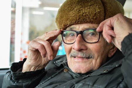 vital: Portrait of active, vital elderly man with gray moustache and fur hat, sitting in a car and adjusting his spectacles