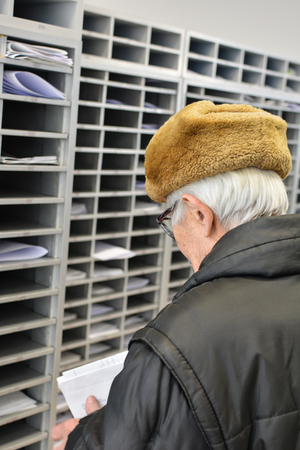 post mail: Active senior in a post office, checking his mail, looking at financial report from a bank Stock Photo
