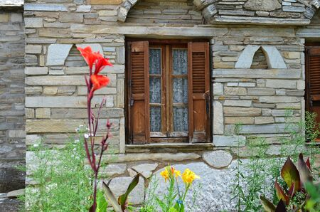 arhitecture: Arhitecture detail, wooden window with shutters on old, vintage stone house with flowers in foreground