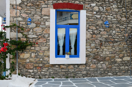 laterns: Greek style blue and white window on stone wall, blue laterns and flowers Stock Photo