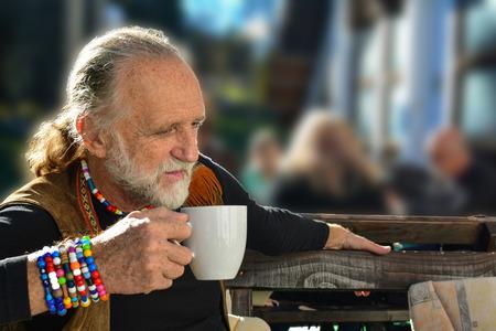 poquito: Apuesto mayor que tiene una taza de café en una terraza del restaurante, mirando un poco ansioso