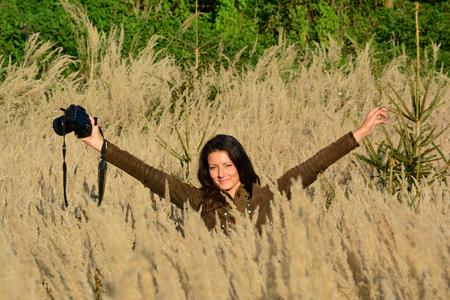 joven muchacha morena de pelo largo fotgrafo de la naturaleza en la hierba de color