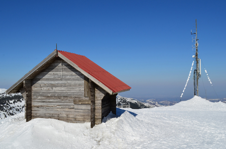 mountin: The end of winter, wooden shelter and antenna on the top of the mountin, sunny day and melting snow Stock Photo