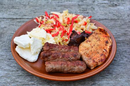 carnes y verduras: Plato saludable, sabrosa y fuerte, filete de pollo y el hígado, cevapcici, productos lácteos y ensalada en placa cerámica marrón en la vieja mesa de roble, vista lateral