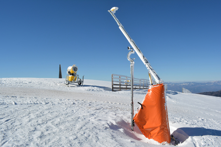 Start of the ski slopes with ramp, high wooden fence, snow cannon and meteorological wind gauge mounted on the ramp