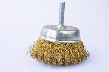 Round brass brush, to be mounted on drilling machine, over white background