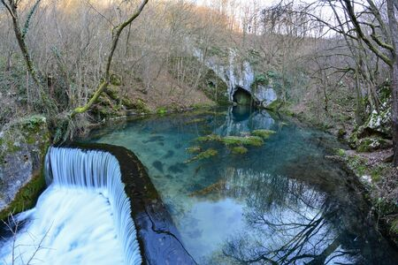 fountainhead: Springhead, cascade and clear, turquoise water of Krupaja river running out from the cave, fisheye landscape, Krupajsko vrelo, Serbia Stock Photo