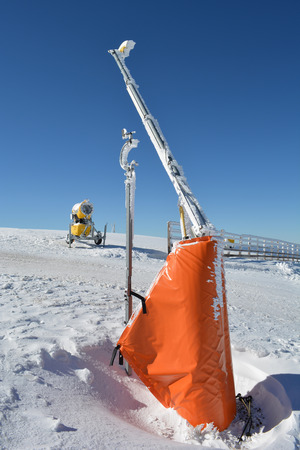 appointed: Start of the ski slopes with ramp, high wooden fence, snow cannon and meteorological wind gauge mounted on the ramp, vertical orientation, Kopaonik, Serbia Stock Photo