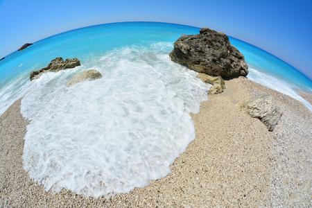 Sunny day on a pebble beach, blue turquoise water, waves, sea foam and a few rocks, fisheye seascape