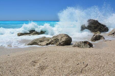 Big, splashing waves embracing rocks in shallow sea on famous Kathisma beach, Lefkada island, Greece 스톡 콘텐츠
