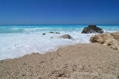 Windy summer day on famous Kathisma beach, Lefkada, beautiful seascape, big waves splashing over stones, turquoise sea and blue, clear sky Stock fotó