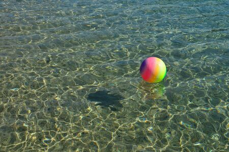 Beach recreation concept, multicolored beach ball floating on the surface of clear, transparent sea water, lot of sparkles, fish-shaped shadow, copy space