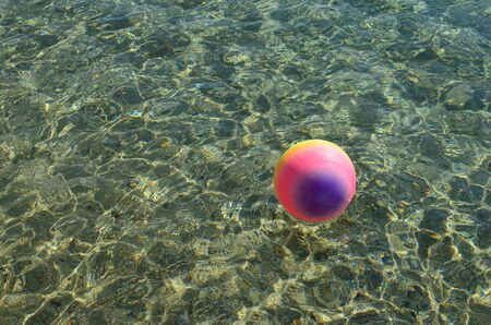 Beach recreation concept, multicolored beach ball floating on the surface of clear, transparent sea water, lot of sparkles, copy space