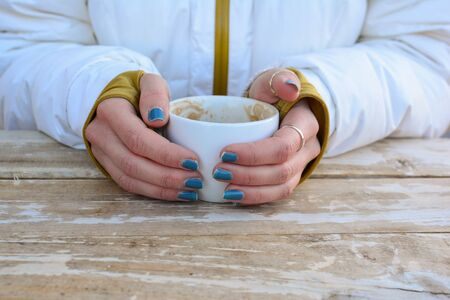 The coffee break is over, empty cuo of coffe in young girl's hands, dressed in white ski suit over white grunge table