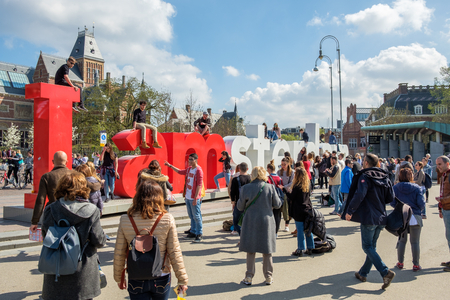 AMSTERDAM, The NETHERLANDS - APR 2, 2017 : Tourists climbing on the letters of the I Amsterdam sign at the Museum square in Amsterdam Editöryel