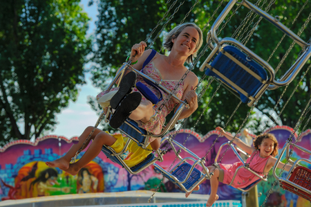 Yearly fair in Ouchy Lausanne. Mother with children have a lot of fun in the carousel