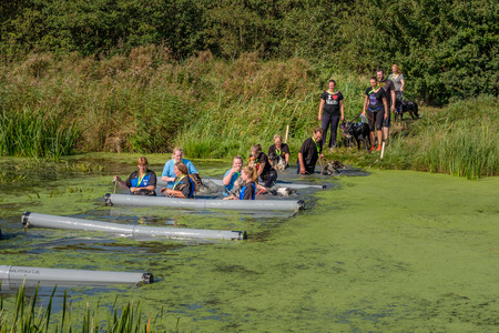 Obstacle course for trainer and dog in a canal. Happy Dog Survival 2016 event in the nature park close to the city of Delft, the Netherlands.