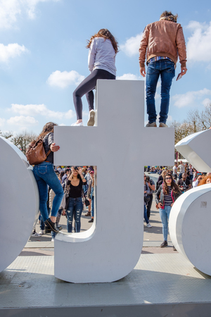 Tourists climb on the iAmsterdam sign at the Museum square, Amsterdam.