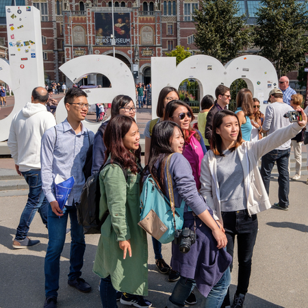 Tourists taking a selfie in front of the iAmsterdam sign at the Museum Square in Amsterdam.