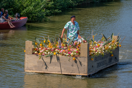 Man in a floating vegetable box, decorated with vegetables and flowers. Yearly parade of boats decorated with vegetables and flowers. Man in a floating vegetable box, decorated with vegetables and flowers.