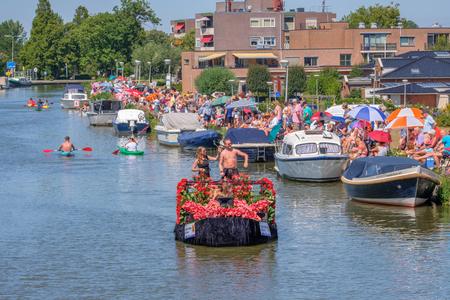 People in canoes during the parade and cheerful people on the quay with nice weather. Yearly parade of boats decorated with vegetables and flowers. Editorial