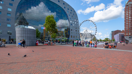View of the outside of the market hall in Rotterdam with a large Ferris wheel and groups of people and cyclists on the square in front of the building. Editorial