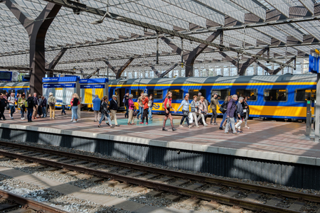 De nombreux passagers sur un quai viennent de quitter le train et se dirigent vers la sortie de la gare centrale de Rotterdam, aux Pays-Bas. Éditoriale