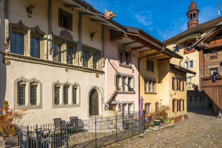Rue de Bourg Gruyeres, Switzerland, the old road up to the Gruyeres castle. Old medieval houses in autumn light. Editoriali