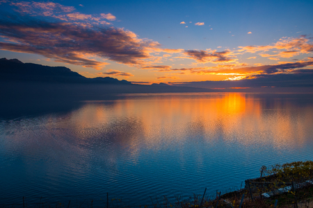 Beautiful colorful sunset in autumn with silhouettes of the French Alps and fantastic orange glowing reflected colors on the Lake Geneva, Switzerland.