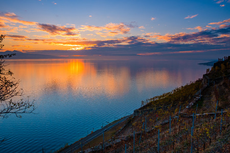 Beautiful colorful sunset in the autumn above the French Alps and Lake Geneva where the colors and clouds reflect nicely. The low sun gives a nice warm light to the vineyards of Lavaux, Switzerland. 스톡 콘텐츠