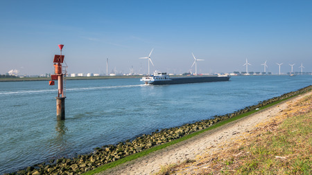 Ship sailing on the New Waterway along industries and wind turbines in the direction of the North Sea. This is the access route for large seagoing vessels from the North Sea to the port of Rotterdam. Stockfoto