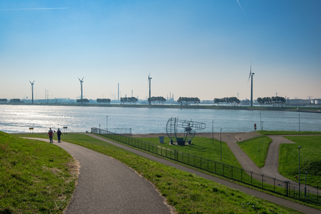 Backlight shot of two people walking on the dike, close to the storm surge, towards the new waterway, the access route for large seagoing vessels from the North Sea to the port of Rotterdam. Stock Photo