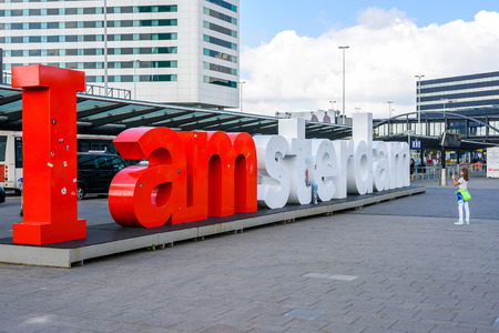 Amsterdam Airport, Schiphol, young female tourist takes a picture of the I Amsterdam sign in front of the passenger terminal of the airport. Editorial