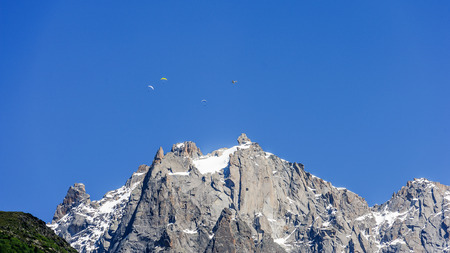 Paragliders above the Mont Blanc massif, seen from the valley near Chamonix, France
