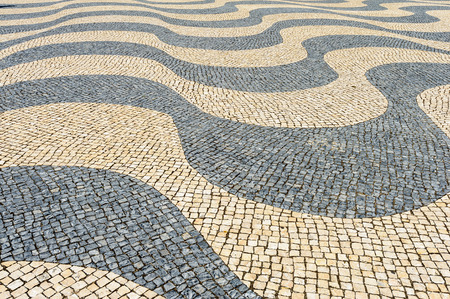 Traditional waving black an white patterns and mosaics of cobblestones on a pavement in Lisbon, Portugal. Stockfoto