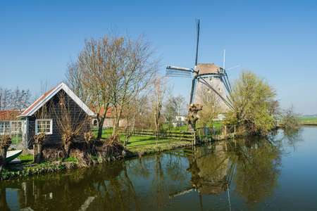 Typical Dutch rural scene with windmill reflected in the water and blue sky. Old still,  functioning polder windmill, very close to Rotterdam, Netherlands. Stockfoto