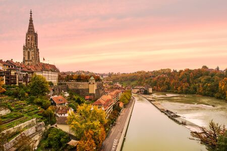 Romantic coloured sunset sky with colourful autumn foliage and historical buildings along the banks of the river Aare in the old city center of Bern, Switzerland