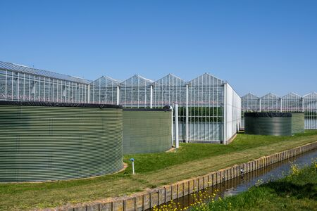 Perspective view of a modern high tech industrial greenhouse for tomatoes with water tanks in front in the Westland, the Netherlands. Westland is a region in of the Netherlands.