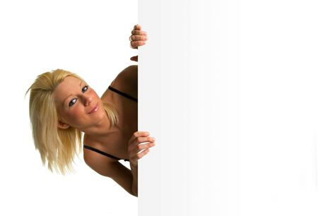 Blonde girl smiling holding a white cartel blank. Ideal to advertising and end season sales messages. photo