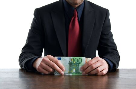 Businessman sitting in office holding in hand a wad of money photo
