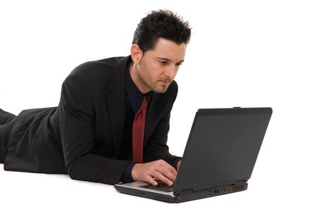 Businessman lying down working with the laptop computer photo